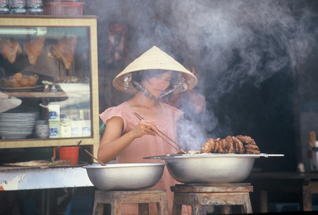 Lady cooking street food in Vietnam